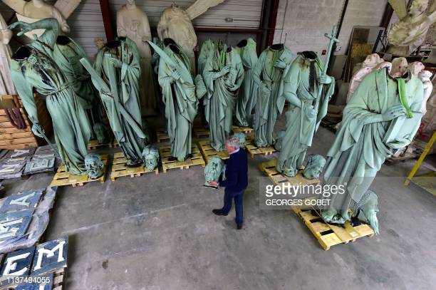 Patrick Palem, expert of the heritage restoration, walks by the statues which sat around the spire of the Notre-Dame cathedral in Paris and removed...