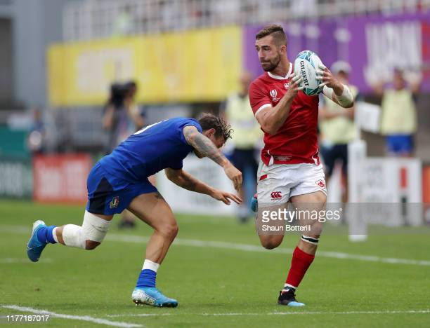 Patrick Parfrey of Canada runs with the ball under pressure from Matteo Minozzi of Italy during the Rugby World Cup 2019 Group B game between Italy...