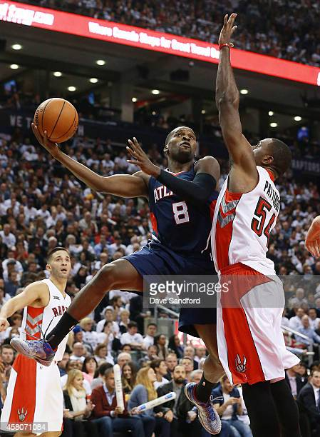 Patrick Patterson of the Toronto Raptors defends against Shelvin Mack of the Atlanta Hawks during their NBA game at the Air Canada Centre on October...