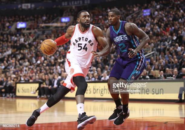 Patrick Patterson of the Toronto Raptors makes a move towards the basket as he is guarded by Marvin Williams of the Charlotte Hornets during NBA game...