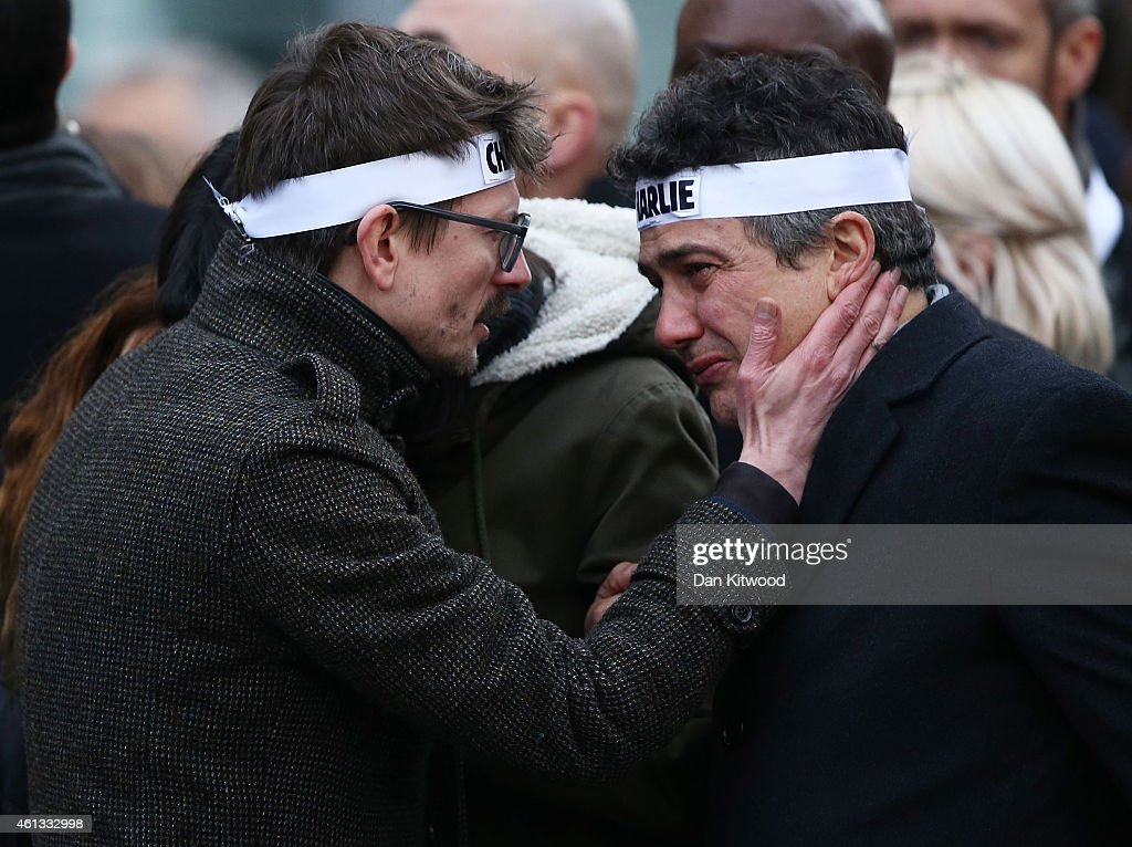 Patrick Pelloux (R), a journalist at Charlie Hebdo, is embraced by Renald 'Luz' Lucier (L), the only surviving cartoonist at the magazine attend a mass unity rally following the recent Paris terrorist attacks on January 11, 2015 in Paris, France. An estimated one million people have converged in central Paris for the Unity March joining in solidarity with the 17 victims of this week's terrorist attacks in the country. French President Francois Hollande led the march and was joined by world leaders in a sign of unity. The terrorist atrocities started on Wednesday with the attack on the French satirical magazine Charlie Hebdo, killing 12, and ended on Friday with sieges at a printing company in Dammartin en Goele and a Kosher supermarket in Paris with four hostages and three suspects being killed. A fourth suspect, Hayat Boumeddiene, 26, escaped and is wanted in connection with the murder of a policewoman.