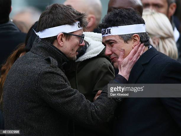 """Patrick Pelloux , a journalist at Charlie Hebdo, is embraced by Renald """"Luz"""" Lucier , the only surviving cartoonist at the magazine attend a mass..."""