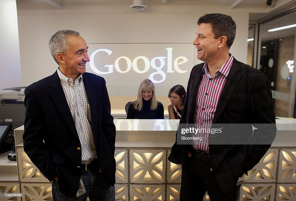 Patrick Pichette, chief financial officer of Google Inc., left, and Chris O'Neil, managing director of Google Inc. Canada, share a laugh at the front desk during a media tour for the grand opening of Google Inc.'s new office in Toronto, Ontario, Canada, on Tuesday, Nov. 13, 2012. The office space encompasses five color-coded floors and features amenities such as a pool table, video games, mini-golf putting greens and a camping lounge where employees can hold meetings in a tent. Photographer: Brett Gunlock/Bloomberg via Getty Images