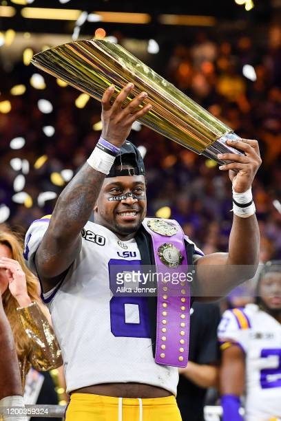 Patrick Queen of the LSU Tigers raises the National Championship Trophy after the College Football Playoff National Championship game against the...