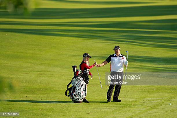 Patrick Reed and his wife and caddie Justine Reed prepare to hit a shot from the fairway during the second round of the Travelers Championship held...