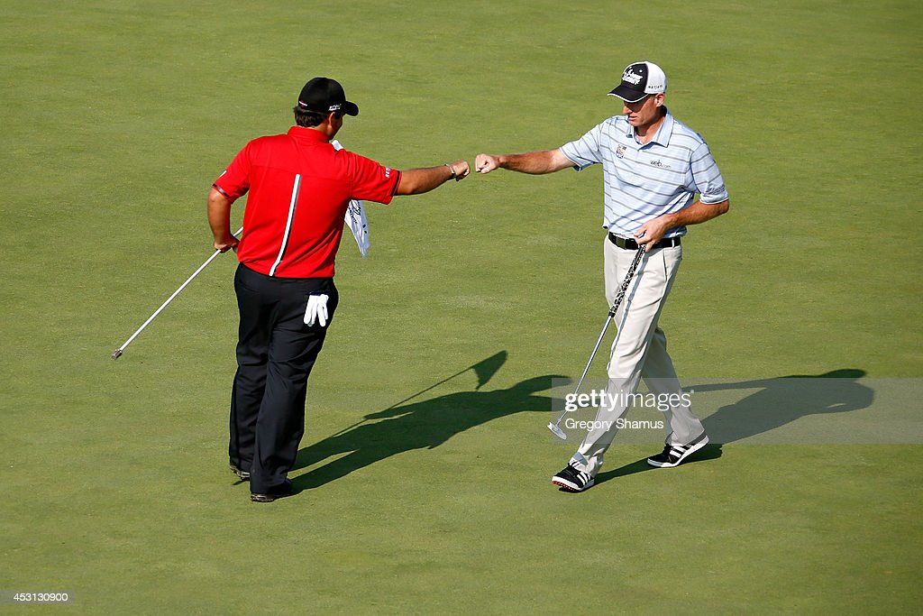 Patrick Reed (L) and Jim Furyk celebrate after Reed's eagle on the 17th green during the final round of the World Golf Championships-Bridgestone Invitational at Firestone Country Club South Course on August 3, 2014 in Akron, Ohio.