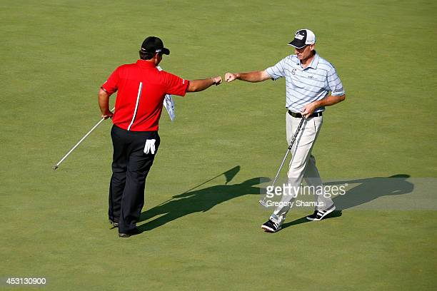 Patrick Reed and Jim Furyk celebrate after Reed's eagle on the 17th green during the final round of the World Golf Championships-Bridgestone...