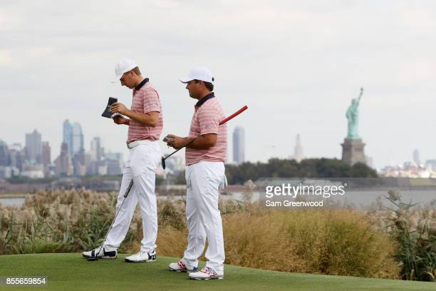 Patrick Reed and Jordan Spieth of the US Team stand on the ninth hole during Friday fourball matches of the Presidents Cup at Liberty National Golf...