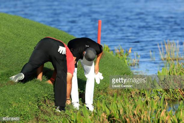 Patrick Reed and Rickie Fowler look for Reed's ball that was embedded in the bank in front of the 11th green during the second round of the 2018...