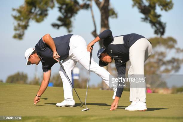 Patrick Reed and Rickie Fowler repair divots on the 11th green on the North course during the first round of the Farmers Insurance Open at Torrey...