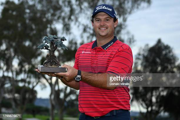 Patrick Reed celebrates with the trophy after winning the Farmers Insurance Open at Torrey Pines South on January 31, 2021 in San Diego, California....