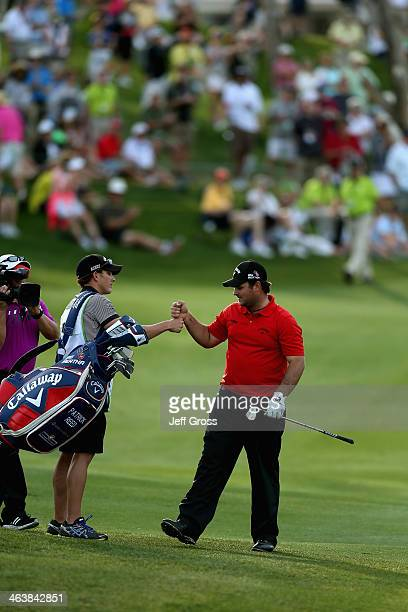 Patrick Reed congratulates his caddy Kessler Karain as they approach the 18th green during the final round of the Humana Challenge in partnership...