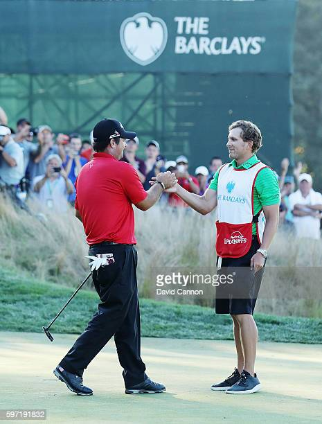Patrick Reed greets his caddie Kessler Karain on the 18th green after winning The Barclays in the PGA Tour FedExCup PlayOffs on the Black Course at...