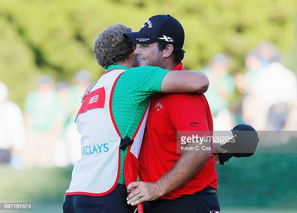 Patrick Reed hugs his caddie Kessler Karain on the 18th green after winning The Barclays in the PGA Tour FedExCup PlayOffs on the Black Course at...