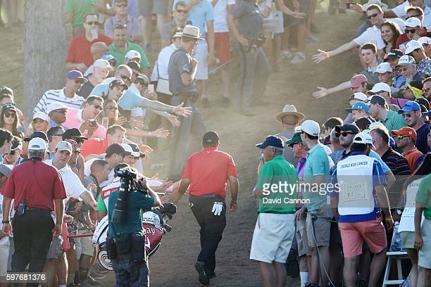 Patrick Reed is greeted by fans as he leaves the 17th green during the final round of The Barclays in the PGA Tour FedExCup PlayOffs on the Black...