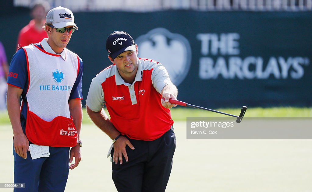 Patrick Reed lines up a putt with his caddie Kessler Karain on the 14th green during the second round of The Barclays in the PGA Tour FedExCup Play-Offs on the Black Course at Bethpage State Park on August 26, 2016 in Farmingdale, New York.