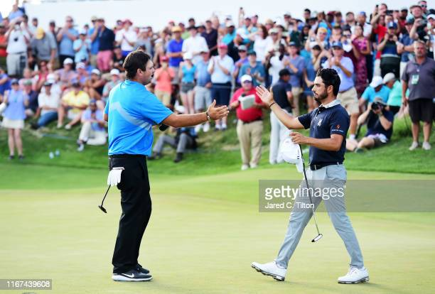 Patrick Reed of the United States and Abraham Ancer of Mexico embrace on the 18th green after Reed won during the final round of The Northern Trust...