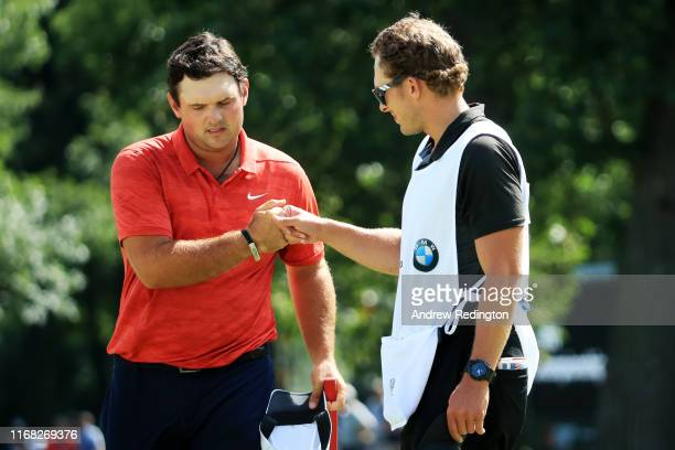 Patrick Reed of the United States and caddie Kessler Karain bump fists on the 18th green during the first round of the BMW Championship at Medinah...