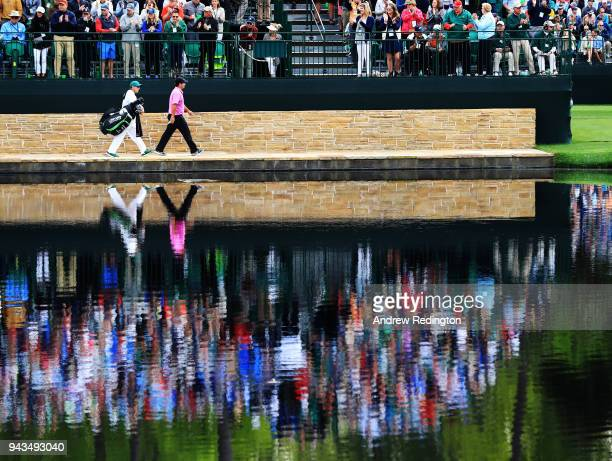 Patrick Reed of the United States and caddie Kessler Karain cross the Sarazen Bridge on the 16th hole during the final round of the 2018 Masters...