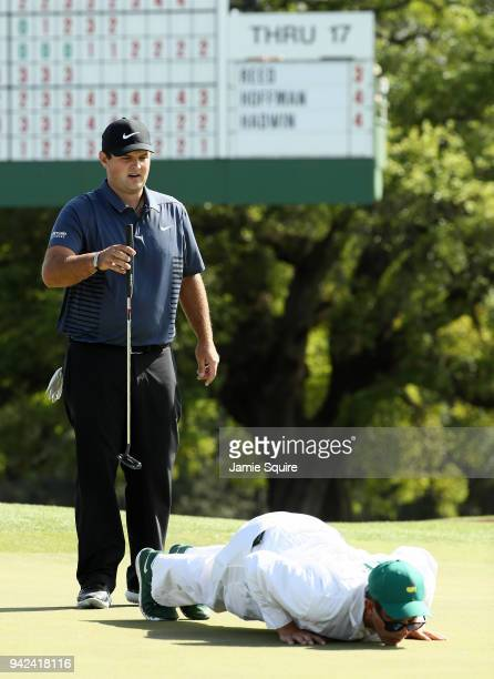 Patrick Reed of the United States and caddie Kessler Karain line up a putt on the 18th green during the first round of the 2018 Masters Tournament at...