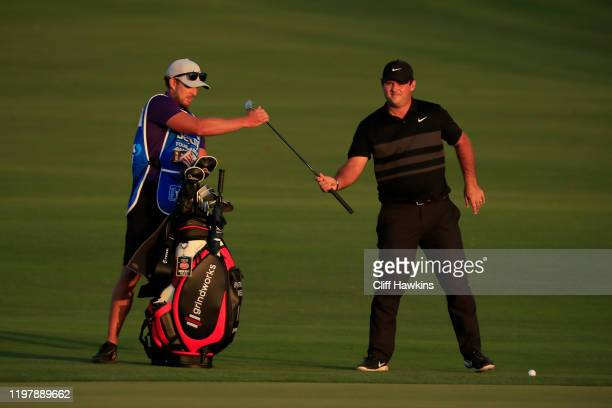 Patrick Reed of the United States and caddie Kessler Karain prepare for a putt onto the 18th green during a playoff in the final round of the Sentry...
