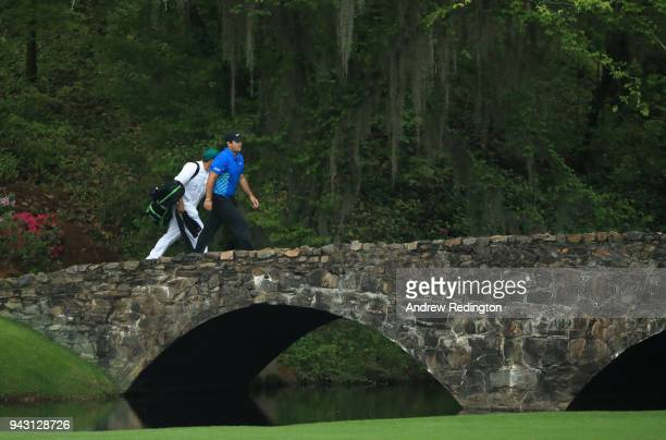 Patrick Reed of the United States and caddie Kessler Karain walk over the Nelson Bridge during the third round of the 2018 Masters Tournament at...