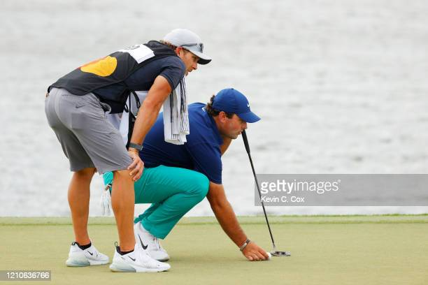 Patrick Reed of the United States and his caddie Kessler Karain line up a putt on the third green during the first round of the Arnold Palmer...