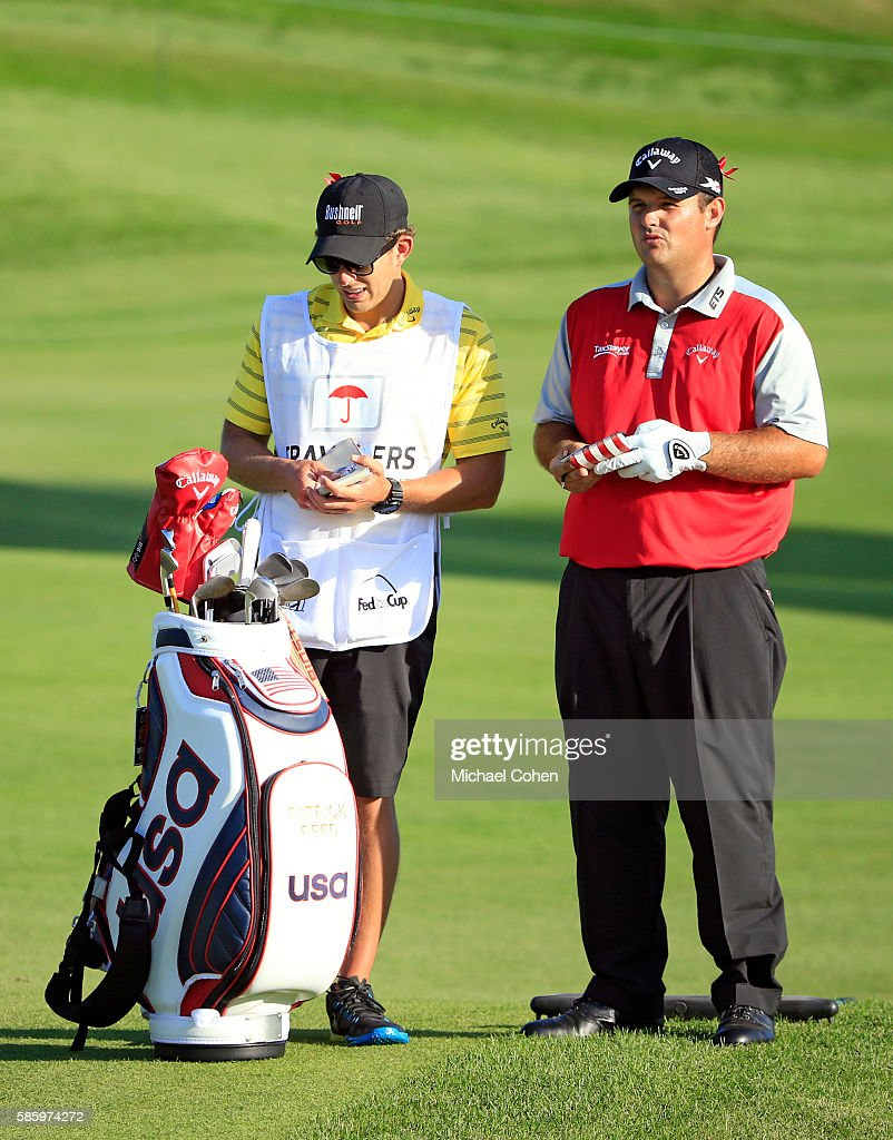 Patrick Reed of the United States and his caddie prepare for his shot on the 18th hole during the first round of the travelers Championship at TPC River Highlands on August 4, 2016 in Cromwell, Connecticut.