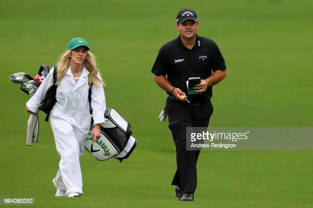 Patrick Reed of the United States and his wife and caddie Justine Karain walk on the eighth tee during a practice round prior to the start of the...