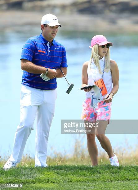 Patrick Reed of the United States and his wife, Justine Karain, talk on the fifth hole during a practice round prior to the 2019 U.S. Open at Pebble...