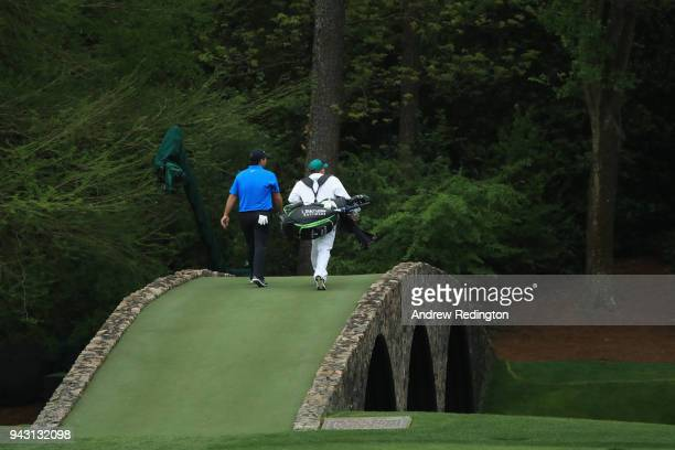 Patrick Reed of the United States and Kessler Karain walk over the Hogan Bridge during the third round of the 2018 Masters Tournament at Augusta...