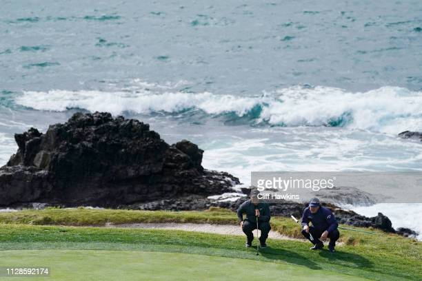 Patrick Reed of the United States and Phil Mickelson of the United States line up putts on the seventh green during the third round of the ATT Pebble...