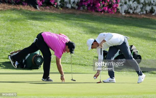 Patrick Reed of the United States and Rory McIlroy of Northern Ireland pick up their golf balls on the 12th green during the final round of the 2018...