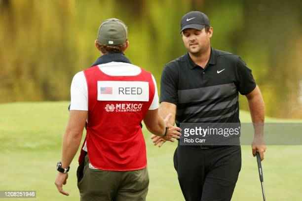 Patrick Reed of the United States celebrates his birdie on the 17th green with caddie Kessler Karain during the final round of the World Golf...