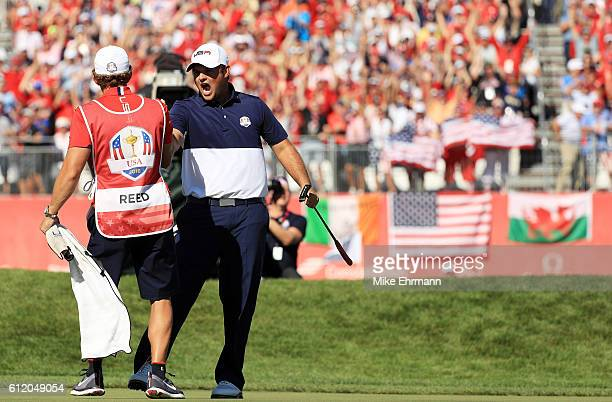 Patrick Reed of the United States celebrates with caddie Kessler Karain after winning his match on the 18th green during singles matches of the 2016...