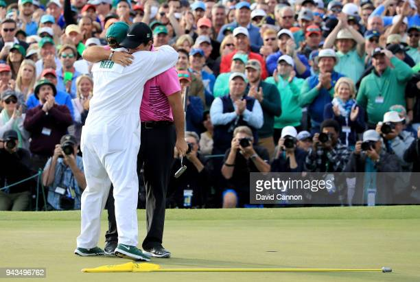 Patrick Reed of the United States celebrates with caddie Kessler Karain after making par 18th green during the final round to win the 2018 Masters...