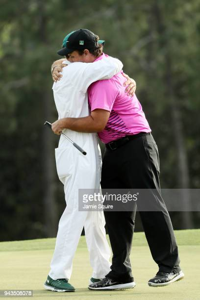 Patrick Reed of the United States celebrates with caddie Kessler Karain after making par on the18th green during the final round to win the 2018...