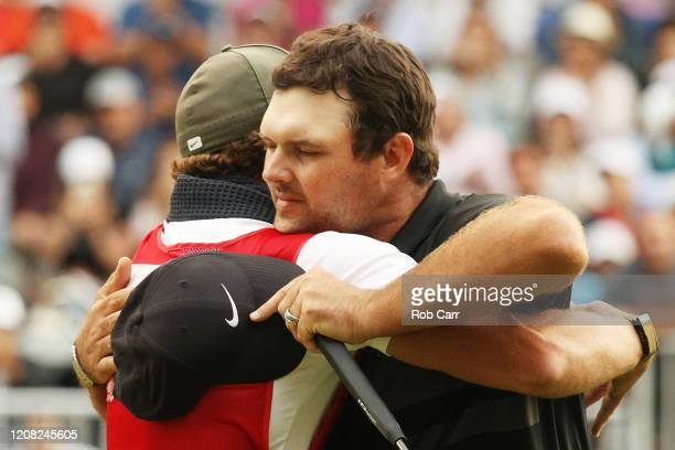 Patrick Reed of the United States celebrates with his caddie Kessler Karain on the 18th green after winning during the final round of the World Golf...