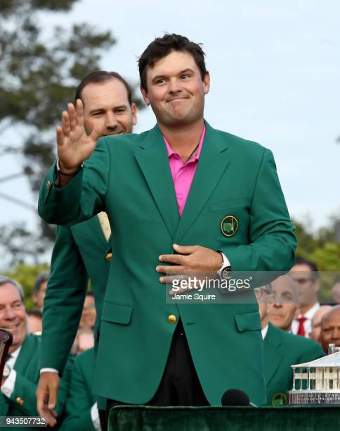 Patrick Reed of the United States is presented with the green jacket by Sergio Garcia of Spain during the green jacket ceremony after winning the...