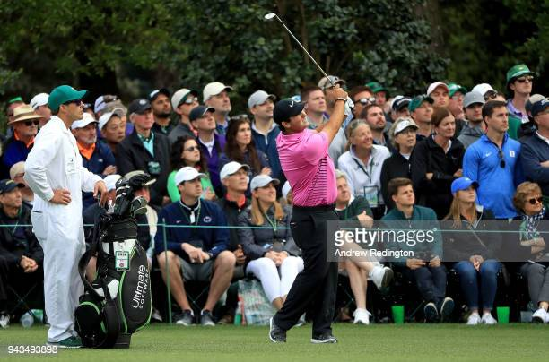 Patrick Reed of the United States plays a shot on the 16th hole as caddie Kessler Karain looks on during the final round of the 2018 Masters...
