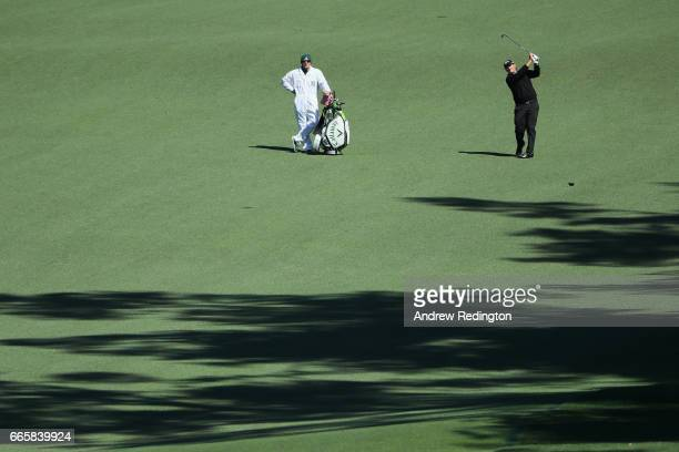 Patrick Reed of the United States plays an approach shot on the second hole as caddie Kessler Karain looks on during the second round of the 2017...