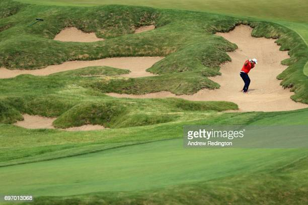 Patrick Reed of the United States plays his shot from a bunker on the 18th hole during the third round of the 2017 US Open at Erin Hills on June 17...