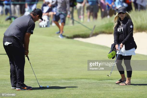 Patrick Reed of the United States putts as his wife Justine Karain looks on during a practice round prior to the 2018 US Open at Shinnecock Hills...