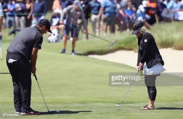 Patrick Reed of the United States putts as his wife Justine Karain looks on during a practice round prior to the 2018 U.S. Open at Shinnecock Hills...