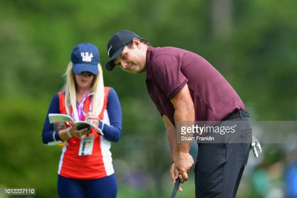 Patrick Reed of the United States putts as wife Justine Karain looks on during a practice round prior to the 2018 PGA Championship at Bellerive...