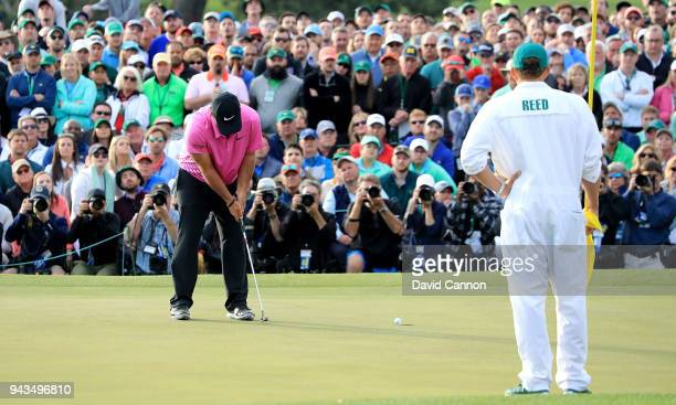 Patrick Reed of the United States putts for par as caddie Kessler Karain looks on during the final round to win the 2018 Masters Tournament at...