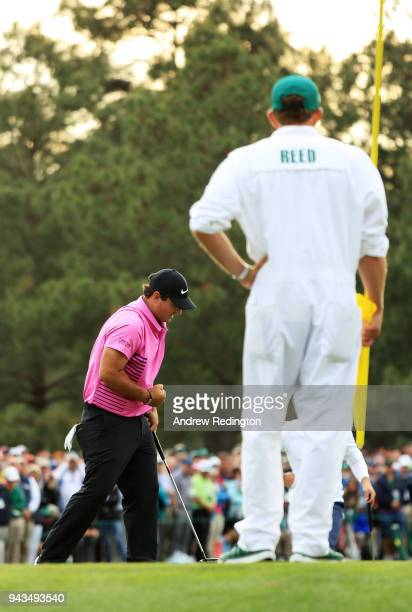 Patrick Reed of the United States reacts on the 17th green as caddie Kessler Karain looks on during the final round of the 2018 Masters Tournament at...
