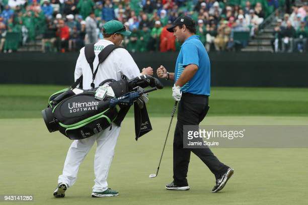 Patrick Reed of the United States reacts to an eagle with caddie Kessler Karain on the 15th green during the third round of the 2018 Masters...
