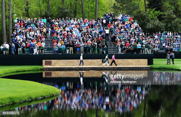 Patrick Reed of the United States Rory McIlroy of Northern Ireland and caddie Kessler Karain cross the Sarazen Bridge on the 16th hole during the...