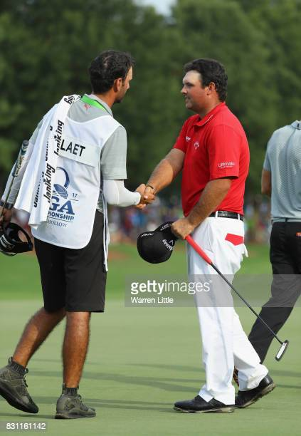 Patrick Reed of the United States shakes hands with Graham DeLaet of Canada's caddie Julien Trudeau during the final round of the 2017 PGA...